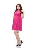 Счастливые детеныши плюс женщина размера представляя в розовом платье Стоковая Фотография