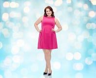 Счастливые детеныши плюс женщина размера представляя в розовом платье Стоковое Изображение