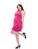 Счастливые детеныши плюс женщина размера представляя в розовом платье Стоковые Изображения RF