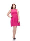 Счастливые детеныши плюс женщина размера представляя в розовом платье Стоковая Фотография RF