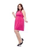 Счастливые детеныши плюс танцы женщины размера в розовом платье Стоковая Фотография