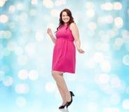 Счастливые детеныши плюс танцы женщины размера в розовом платье Стоковые Изображения RF