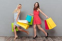 Счастливые детеныши 2 друз дам держа хозяйственные сумки Стоковое фото RF