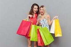 Счастливые детеныши 2 друз дам с хозяйственными сумками используя чернь Стоковая Фотография