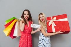 Счастливые детеныши 2 друз дам с хозяйственными сумками и подарком Стоковые Фотографии RF