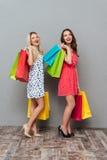 Счастливые детеныши 2 друз дам с хозяйственными сумками Стоковое Изображение RF