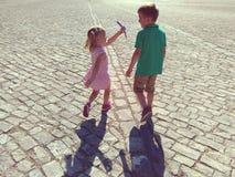 Счастливые дети бежать в солнечном городке Стоковая Фотография RF