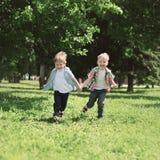 Счастливые дети 2 брать мальчиков бежать совместно и имея потеху Стоковое Фото