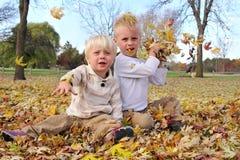 Счастливые дети бросая листья дерева клена падения на камеру Стоковые Фотографии RF