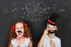 Счастливые дети близнецов держат усик масленицы и бороду, день отца co стоковая фотография