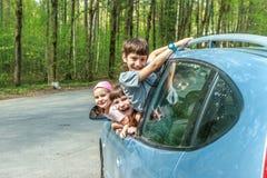 счастливые дети в автомобиле, отключении семьи, перемещении летних каникулов Стоковое Фото