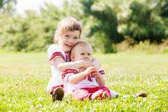 Счастливые дети в русских фольклорных одеждах на луге Стоковые Изображения RF