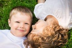 Счастливые дети лежа на зеленой траве Стоковые Изображения RF