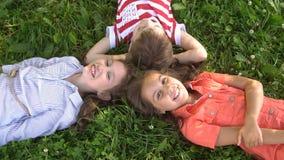 Счастливые дети лежа на траве смеясь над совместно, замедленное движение видеоматериал