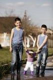 Счастливые дети играя в лужице стоковые фотографии rf