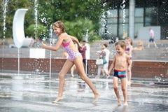 Счастливые дети играя в фонтане Стоковые Фото