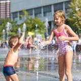 Счастливые дети играя в фонтане Стоковые Изображения RF