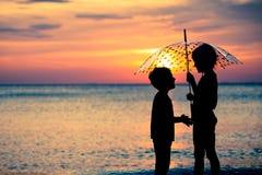 Счастливые дети играя на пляже на времени захода солнца Стоковое фото RF