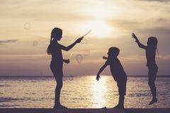 Счастливые дети играя на пляже на времени захода солнца Стоковые Изображения RF