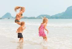 Счастливые дети играя на пляже стоковые изображения rf