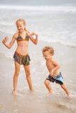 Счастливые дети играя на пляже стоковое изображение