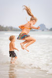 Счастливые дети играя на пляже стоковые фото
