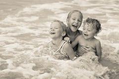 Счастливые дети играя на пляже стоковая фотография