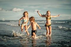 Счастливые дети играя на пляже стоковые фотографии rf
