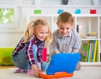 Счастливые дети играя с компьтер-книжкой дома Стоковое Изображение