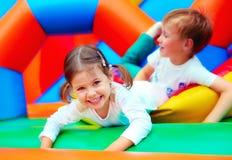 Счастливые дети имея потеху на спортивной площадке в детском саде