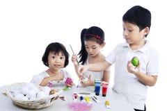 Счастливые дети крася пасхальные яйца Стоковые Изображения RF