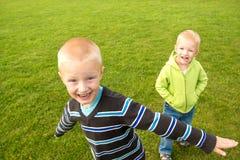 Счастливые дети (мальчики, братья) играя на зеленой траве Стоковая Фотография RF