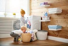 Счастливые дети мальчик и девушка в прачечной нагружают стиральную машину стоковое фото