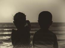 Счастливые дети на заходе солнца морем Стоковые Изображения