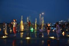Счастливые дети плавая в фонтане стоковое фото