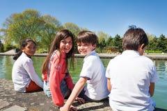Счастливые дети сидя на обваловке реки Стоковое Фото