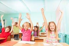 Счастливые дети с оружиями вверх сидят в строках класса Стоковые Изображения RF