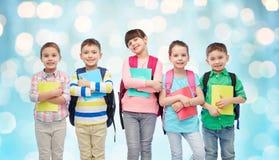 Счастливые дети с сумками и тетрадями школы Стоковые Изображения RF