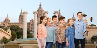 Счастливые дети с smartphone и ручкой selfie Стоковые Фотографии RF