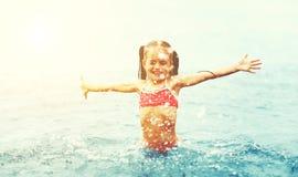 Счастливые детские игры и заплывы девушки с брызгают на пляже Стоковое Изображение RF