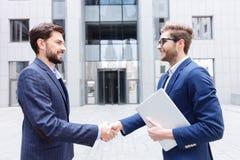 Счастливые 2 делового партнера приветствуя один другого Стоковое Фото