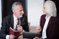 Счастливые деловые партнеры обсуждая проект и обменивая идеи Стоковые Изображения RF