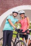 Счастливые женские кавказские велосипедисты стоя Outdoors усмехающся Стоковая Фотография RF
