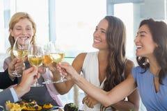 Счастливые женские коллеги провозглашать стекла пива пока имеющ обед Стоковые Изображения