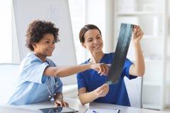 Счастливые женские доктора с рентгеновским снимком отображают на больнице Стоковое фото RF
