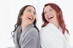 Счастливые женские друзья в купальных халатах стоя спина к спине Стоковые Изображения RF
