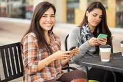 Счастливые женские друзья используя мобильный телефон Стоковые Фотографии RF