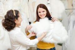 Счастливые женщины выбирают накидку меха на магазине свадьбы Стоковое Изображение RF