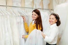Счастливые женщины выбирают bridal одежды на магазине свадьбы. Стоковая Фотография RF