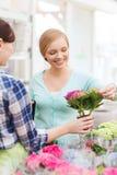 Счастливые женщины выбирая цветки в парнике или магазине Стоковые Изображения
